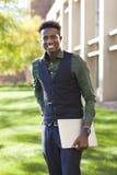 英俊的年轻黑人学生人微笑站立在学院阵营 免版税库存图片