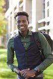 英俊的年轻黑人学生人微笑站立在学院阵营 免版税库存照片