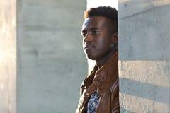 英俊的年轻黑人站立在混凝土桩之间 免版税库存照片