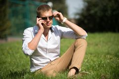 英俊的强壮男子享受夏日 在太阳镜的商人在晴朗室外 人在绿草放松 时尚样式和 库存照片