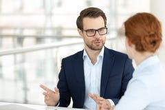 英俊的微笑的男性办公室工作者谈话与女性同事 免版税库存照片