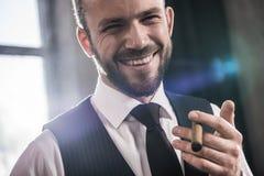 英俊的微笑的确信的人抽烟的雪茄户内 免版税库存照片