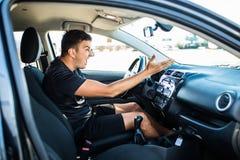英俊的恼怒的司机,当推进汽车在城市时 消极人的情感面孔表示 免版税图库摄影