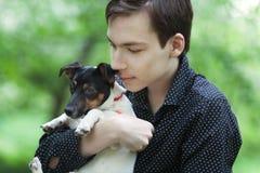 英俊的愉快的少年和狗杰克罗素画象  免版税库存照片
