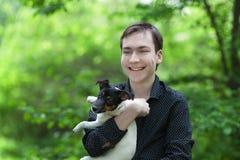 英俊的愉快的少年和狗杰克罗素画象  免版税库存图片