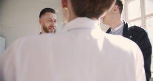 英俊的成功的中部变老了商人谈话与年轻千福年的伙伴在舒适的轻的现代顶楼办公室 股票录像