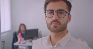 英俊的成功的白种人商人特写镜头画象在看照相机的镜片的在白色办公室 影视素材