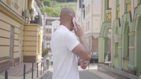 英俊的成功的确信的秃头中东人画象讲话由在街道上的手机身分  影视素材