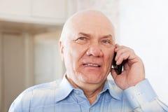 英俊的成熟人告诉由电话 免版税库存照片