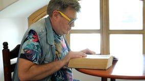 英俊的成熟人坐在桌和纸卷上通过厚实的旧书 股票录像