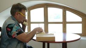 英俊的成熟人坐在桌和纸卷上通过厚实的旧书 股票视频