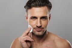 英俊的成熟人照料他的皮肤 库存图片