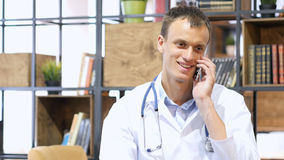 英俊的成熟医生与智能手机的患者协商 免版税库存图片