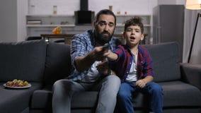 英俊的战斗为电视的爸爸和儿子遥控 股票录像