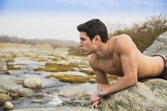 英俊的放置在岩石的适合赤裸上身的年轻人 免版税库存照片