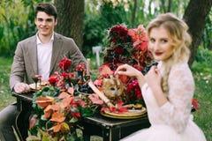 英俊的新郎在欢乐桌上坐被弄脏的新娘背景 秋天婚礼 库存照片