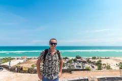 英俊的旅客人逗留在蓝色海洋背景-放松在海观点的愉快的人旁边-自由的概念和 库存图片