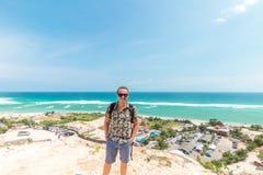 英俊的旅客人逗留在蓝色海洋背景-放松在海观点的愉快的人旁边-自由的概念和 免版税库存图片