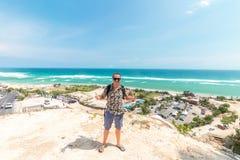 英俊的旅客人逗留在蓝色海洋背景-放松在海观点的愉快的人旁边-自由的概念和 免版税库存照片