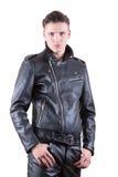英俊的时尚人,秀丽男性式样画象穿戴黑色皮夹克和裤子,白色的年轻人隔绝了背景 库存图片