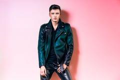 英俊的时尚人画象、摆在墙壁附近的美好的男性式样穿戴黑色皮夹克、气喘和T恤杉 图库摄影