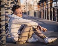 英俊的时髦年轻人,坐一条边路在城市 免版税图库摄影