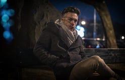 英俊的时髦年轻人,坐长凳在晚上 免版税库存图片