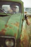 年轻英俊的时髦的人、佩带的衬衣和太阳镜,驾驶老汽车 免版税库存照片