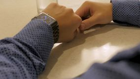 英俊的时髦的在电子手表的男性处理的时间 检查现代腕子时钟的年轻人 免版税图库摄影