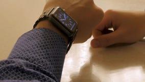 英俊的时髦的在电子手表的男性处理的时间 检查现代腕子时钟的年轻人 免版税库存图片