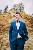 英俊的时髦的新郎特写镜头画象蓝色衣服的与作为背景的一个岩石自然风景 库存照片