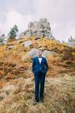 英俊的时髦的新郎画象蓝色衣服的与作为背景的一个岩石自然风景 免版税库存照片