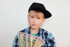 英俊的时髦的liitle富有的孩子照片在黑盖帽和现代衬衣在他的手上的穿戴了拿着美元 年轻businessma 图库摄影