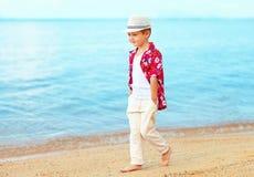英俊的时兴的孩子,走在沙滩的男孩 库存图片