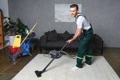 英俊的有吸尘器和微笑的年轻人清洗的白色地毯 免版税库存图片