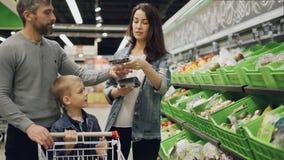 英俊的有胡子的人、他可爱的妻子和逗人喜爱的孩子在超级市场选择在盘子的菜,谈话 影视素材