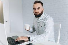 英俊的有胡子的商人与在办公室、饮用的咖啡和放松的膝上型计算机一起使用 图库摄影
