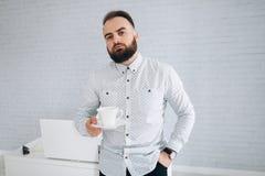 英俊的有胡子的商人与在办公室、饮用的咖啡和放松的膝上型计算机一起使用 免版税库存图片