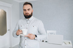 英俊的有胡子的商人与在办公室、饮用的咖啡和放松的膝上型计算机一起使用 库存图片