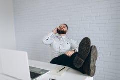 英俊的有胡子的商人与在办公室和叫的膝上型计算机一起使用 免版税库存图片
