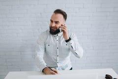 英俊的有胡子的商人与在办公室和叫的膝上型计算机一起使用 免版税库存照片
