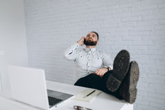 英俊的有胡子的商人与在办公室和叫的膝上型计算机一起使用 库存照片