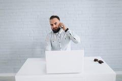 英俊的有胡子的商人与在办公室和叫的膝上型计算机一起使用 库存图片