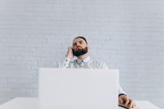 英俊的有胡子的商人与在办公室和叫的膝上型计算机一起使用 图库摄影