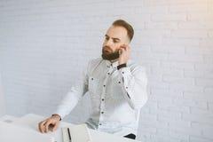 英俊的有胡子的商人与在办公室,饮用的咖啡和叫的膝上型计算机一起使用 库存照片