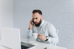 英俊的有胡子的商人与膝上型计算机一起使用在办公室 免版税图库摄影