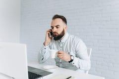 英俊的有胡子的商人与膝上型计算机一起使用在办公室 免版税库存图片
