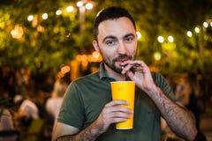 英俊的有胡子的欧洲人饮用的coctail或啤酒在室外街道咖啡馆夜党在公园 库存图片