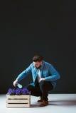 年轻英俊的有胡子的男性行家,打扮在牛仔布衬衣,坐户内和洒从浪花的花 库存图片