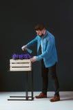 年轻英俊的有胡子的男性行家,打扮在牛仔布衬衣,站立户内并且洒从浪花的花 免版税库存照片